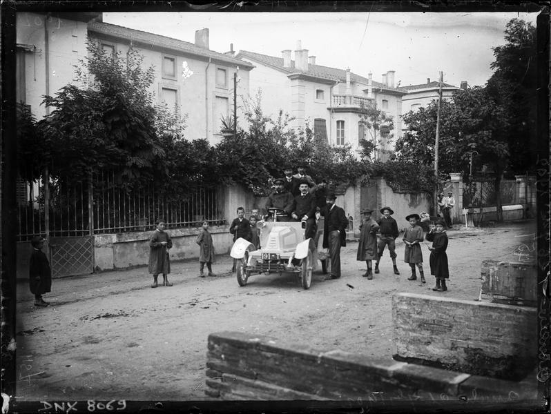 Automobile à l'arrêt avec son chauffeur et ses passagers dans une rue de la ville