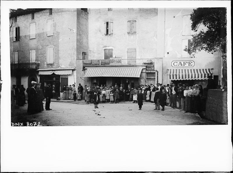 Groupe de villageois sur une place bordée de vieilles maisons et d'un café
