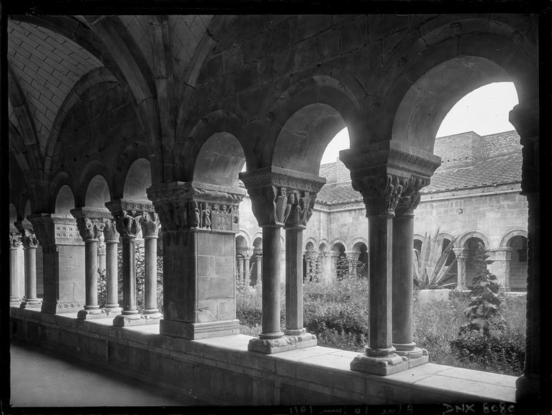 Cloître : colonnettes et piliers d'une galerie vus vers le jardin
