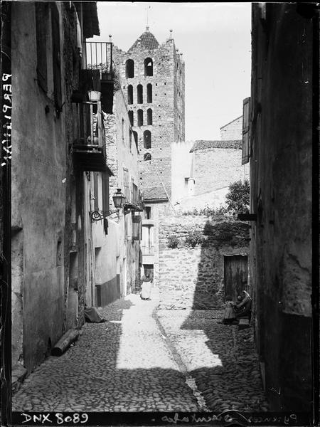 Clocher-tour de l'église abbatiale au bout de la perspective d'une ruelle pavée