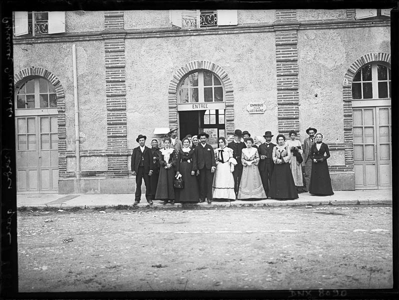 Groupe d'hommes et de femmes devant l'entrée de la gare