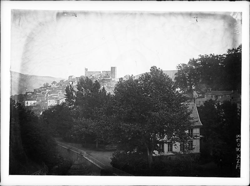 Parc et maisons au premier plan, village, église et château à l'arrière-plan