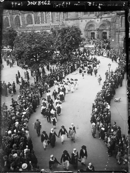 Défilé de costumes traditionnels alsaciens, façade sud de la cathédrale et portail de l'horloge astronomique en arrière-plan