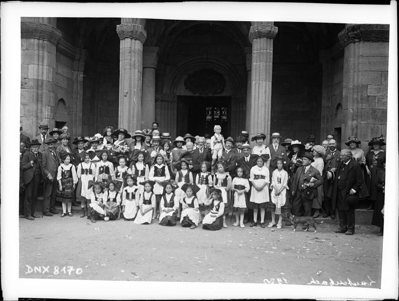 Congrès de 1920, portrait collectif : congressistes et femmes en costume traditionnel alsacien devant le porche de l'église