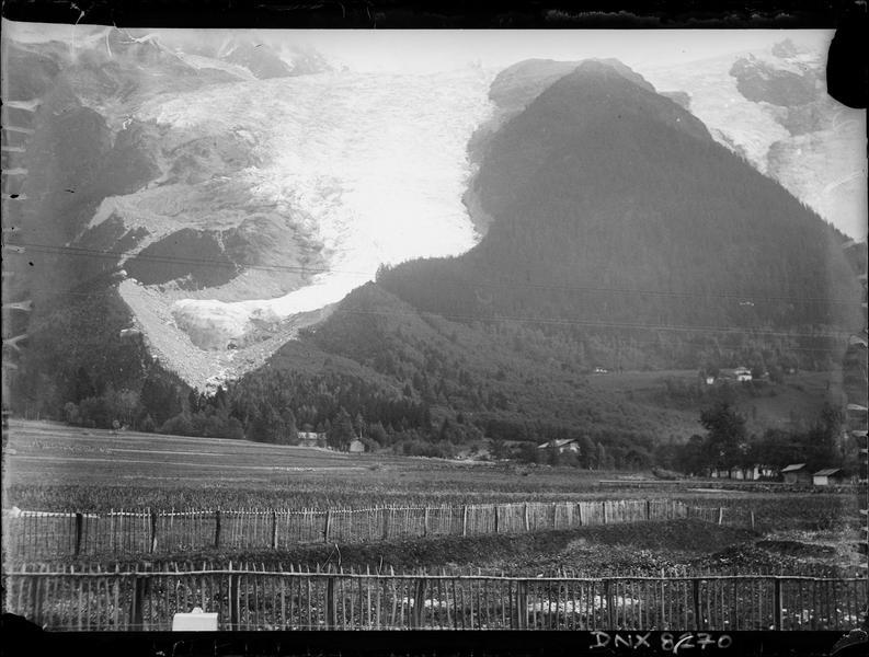 Paysage de montagne aux environs d'Annecy : champs et clôtures en contrebas de pentes boisées