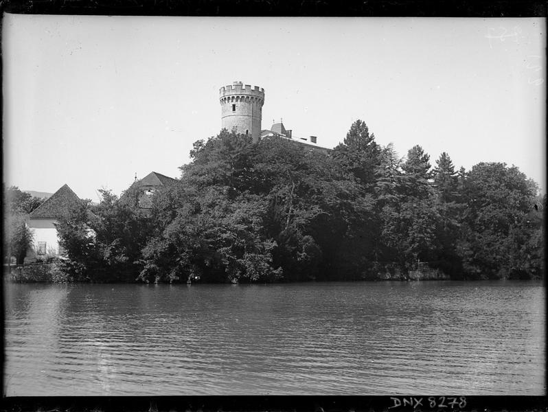 Tour crénelée et toitures dominant les arbres au-dessus du lac