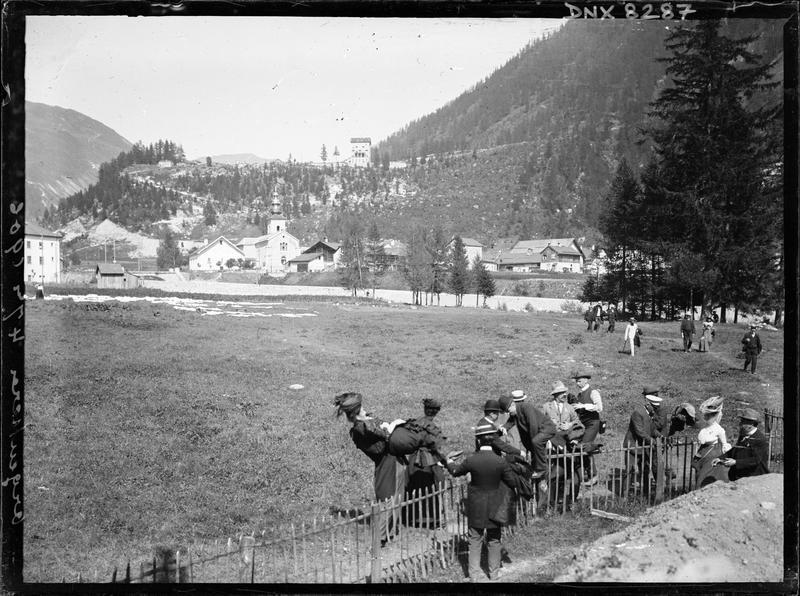 Paysage de montagne : le village d'Argentière, groupe de promeneurs franchissant une barrière au premier plan