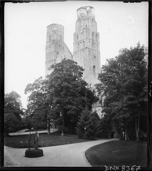Ruines de l'église abbatiale : tours de la façade ouest, puits au premier plan