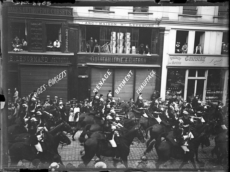 Défilé militaire : musiciens à cheval dans une rue commerçante