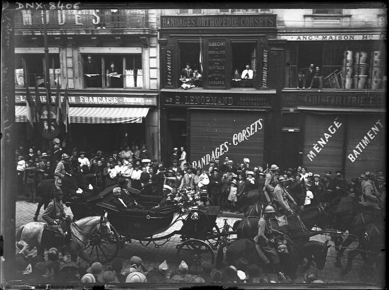 Défilé militaire : soldats à cheval et calèche dans une rue commerçante