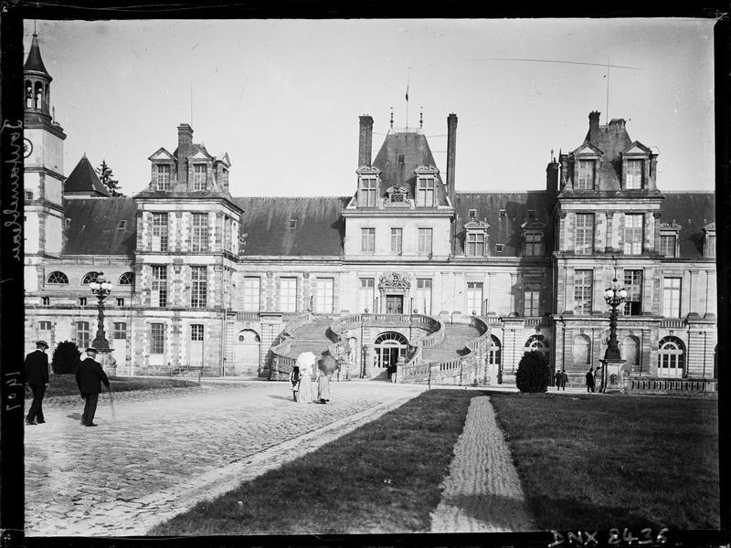Façade sur la cour du Cheval Blanc ou cour des Adieux : visiteurs se dirigeant vers l'escalier en fer à cheval