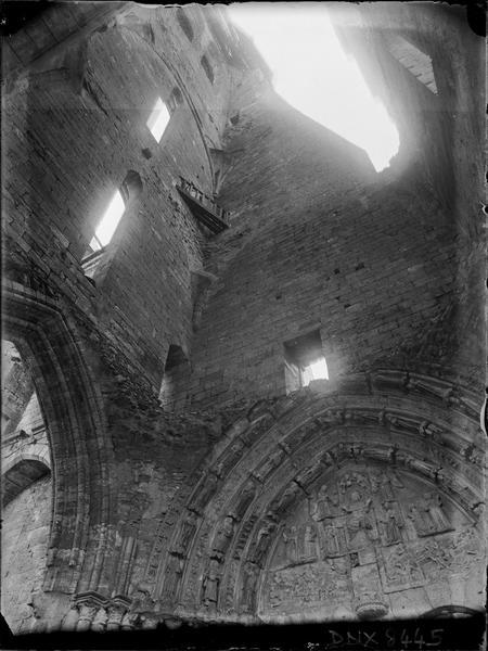 Intérieur de la tour en ruines et tympan du portail vus en contre-plongée