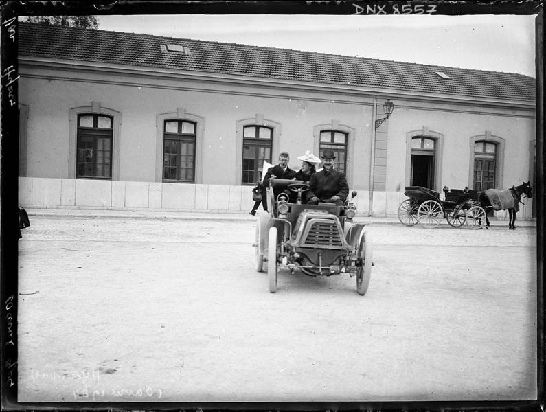 Automobile et véhicule hippomobile devant la gare