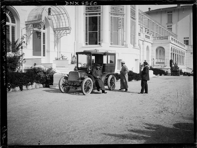 Automobile et son chauffeur devant l'entrée