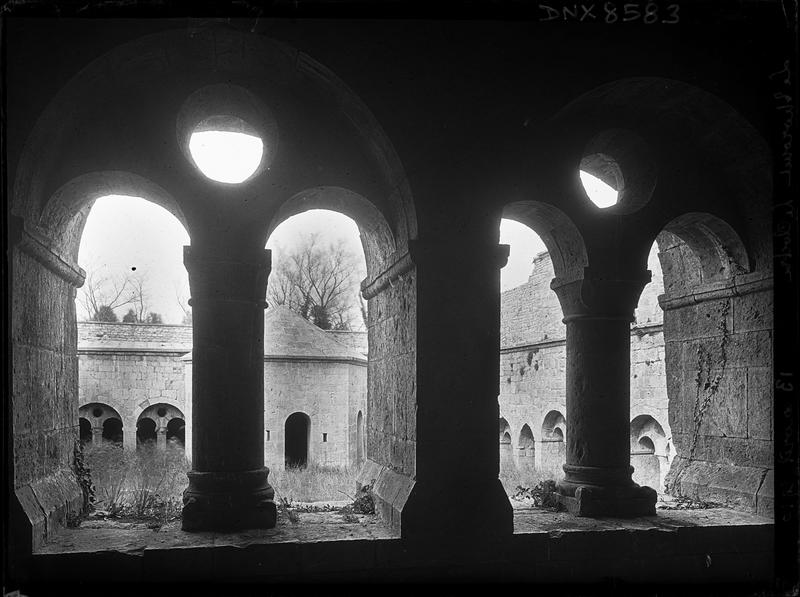 Cour du cloître et lavabo vus à travers deux arcatures géminées d'une galerie
