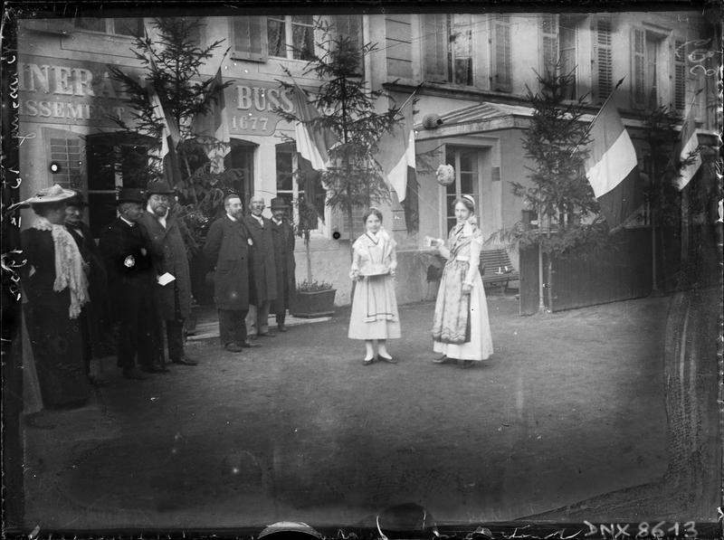 Visiteurs et deux femmes en costume régional devant la façade