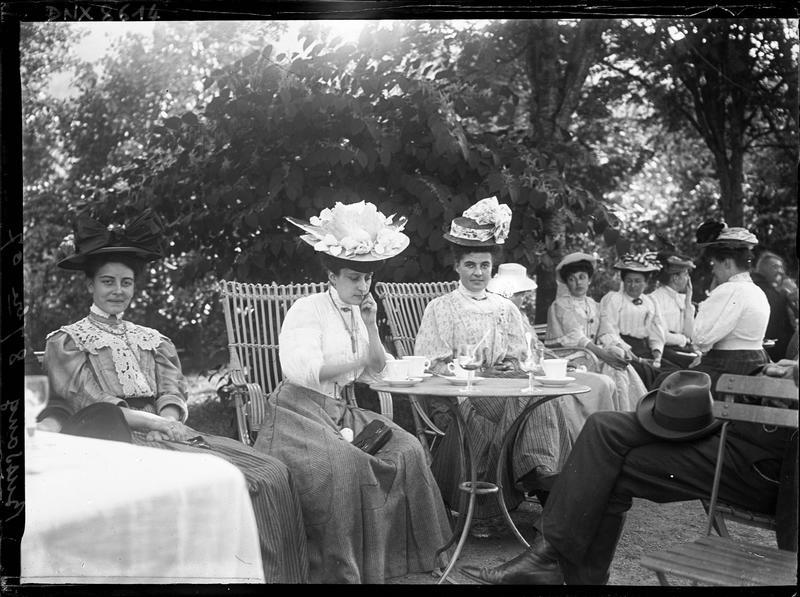 Dames assises en plein air autour d'un guéridon, arbustes à l'arrière-plan