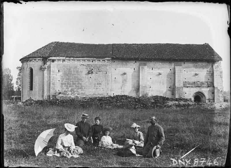 Façade nord, groupe de promeneurs assis dans l'herbe au premier plan