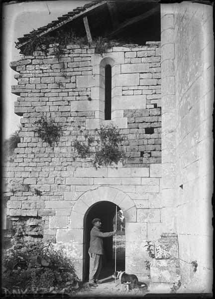 Bâtiment jouxtant l'abside au sud, homme mesurant un portail avec une perche