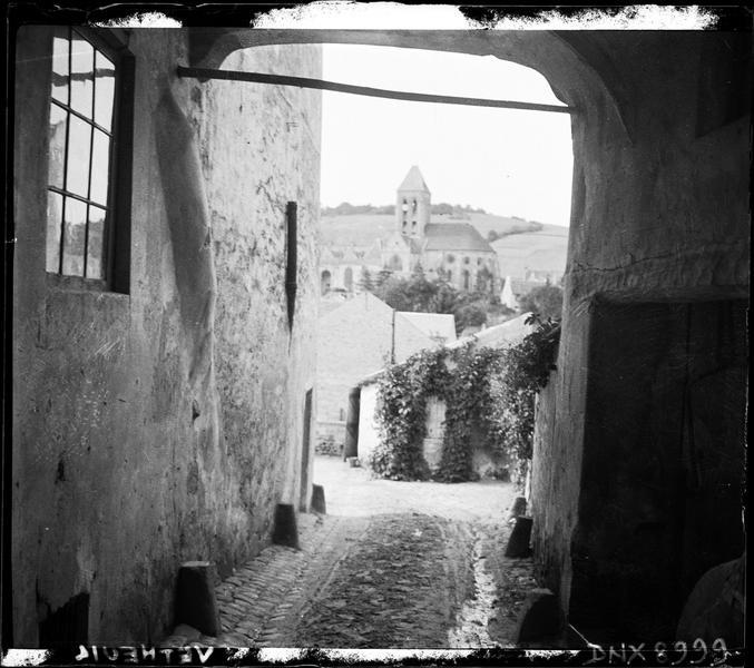 Ruelle et arcade, l'église en arrière-plan