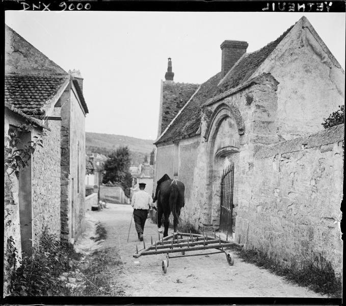 Rue du village : cheval attelé à une herse, porche ancien