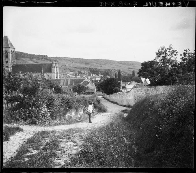 Chemin à l'orée du village, église en arrière-plan