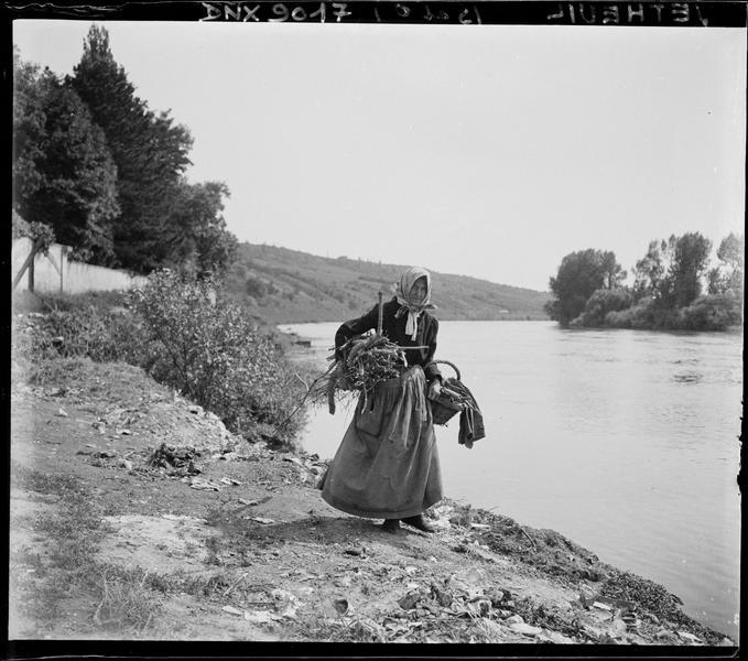 Paysanne au fagot et au panier, sur un talus dominant la Seine