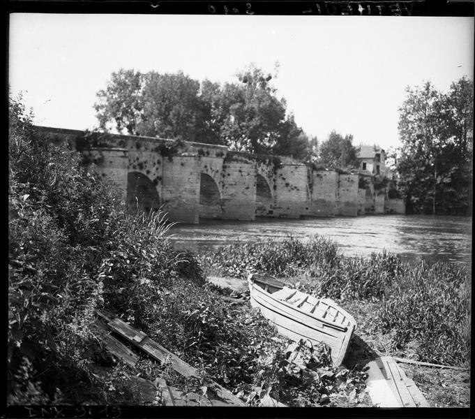 Le pont vu des berges de la Seine, barques échouées au premier plan