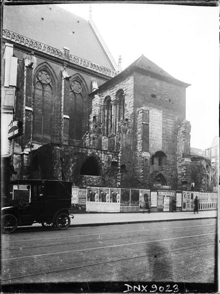 Partie de la façade sud, clocher, palissade tapissée d'affiches