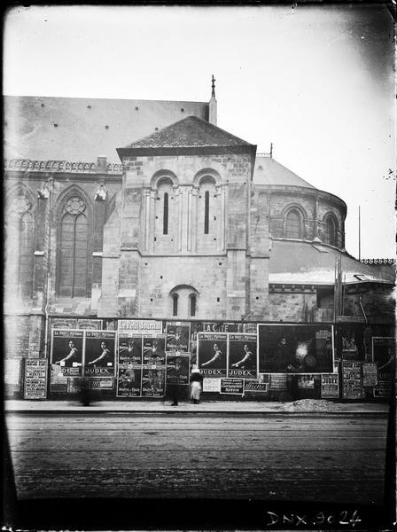 Partie de la façade sud et de l'abside, clocher, palissade tapissée d'affiches
