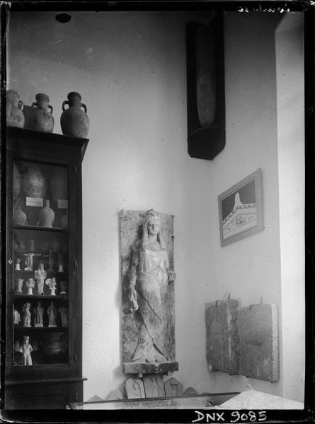 Statue de femme, vitrine de statuettes et de céramiques