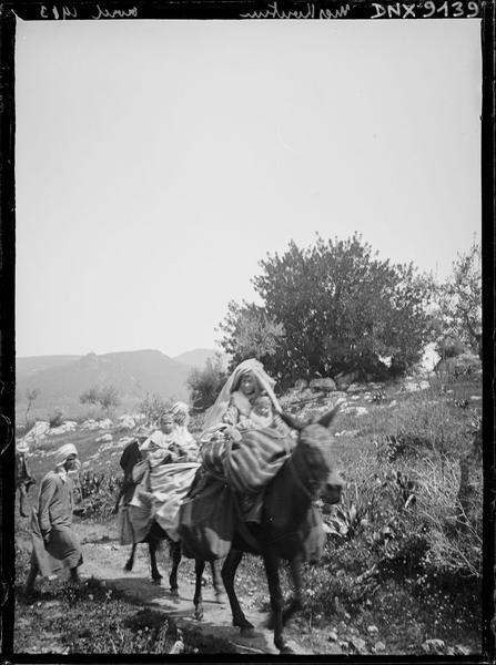 Femmes et enfants juchés sur des ânes
