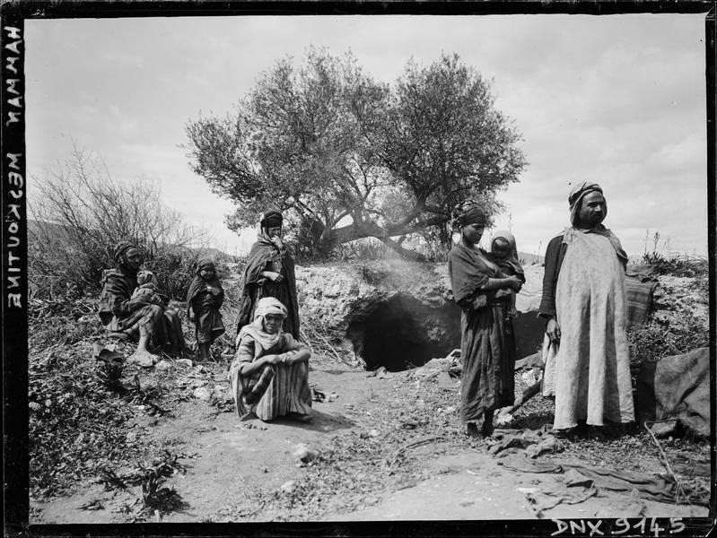 Portrait collectif : famille en costume traditionnel, devant l'entrée d'une grotte