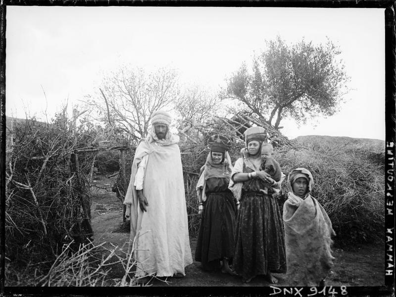 Portrait collectif : famille en costume traditionnel devant des huttes de branchages