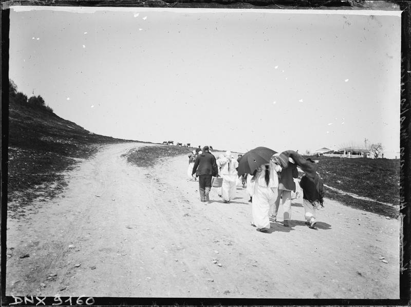 Groupe de personnages vus de dos, cheminant sur une route