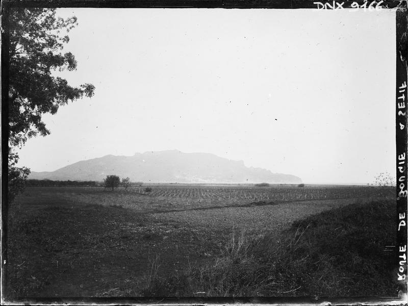 Route de Bougie à Sétif : plaine cultivée, montagnes à l'arrière-plan