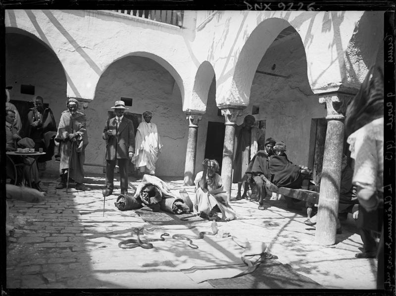 Charmeur de serpents et son public, dans un patio entouré d'arcades