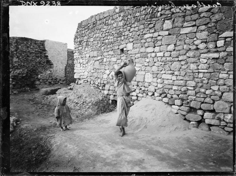 Mur de pierre sur le site archéologique, enfant et femme portant une jarre