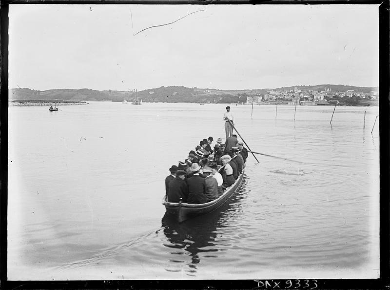 Barque en mer, remplie de passagers, la côte en arrière-plan