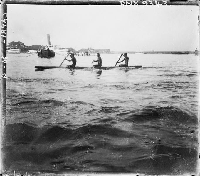 Trois adolescents ramant sur un canoë