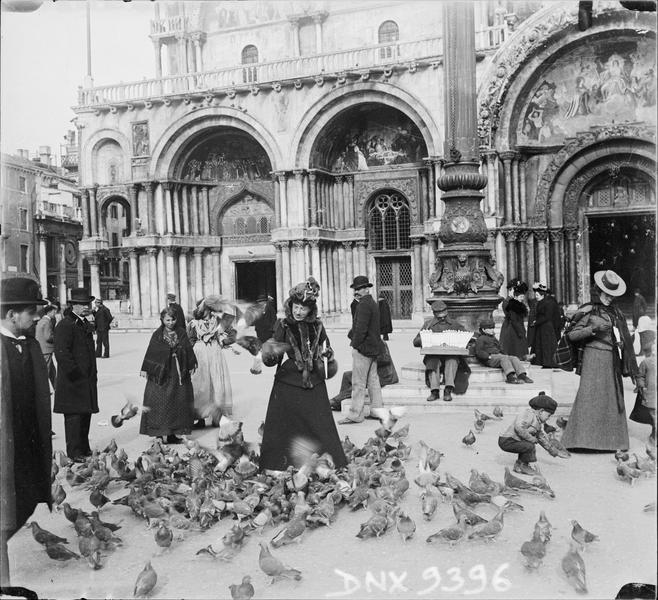 Femme nourrissant des pigeons devant la basilique