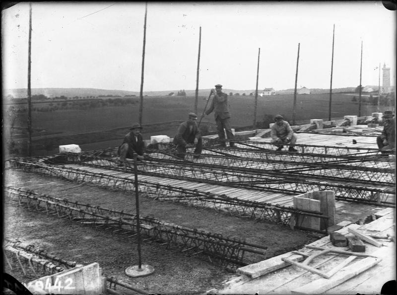 Construction de l'école : ouvriers sur le toit parmi des armatures métalliques