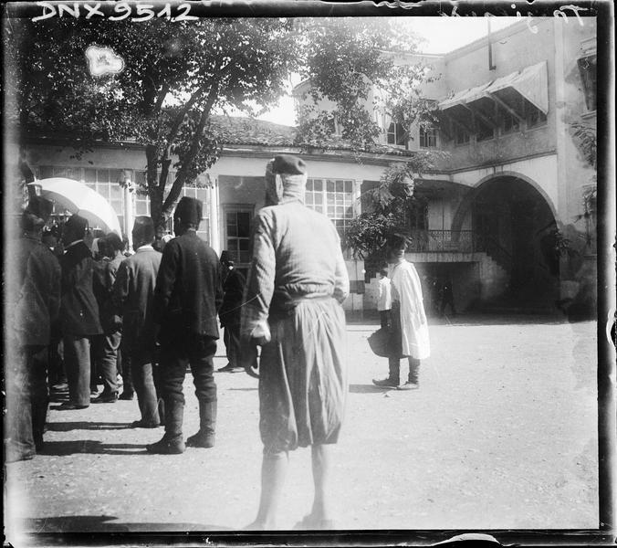 Groupe d'hommes vus de dos, coiffés du Fez