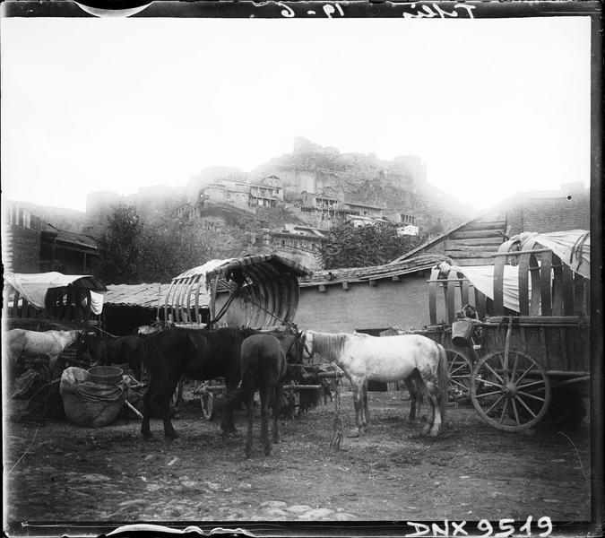 Chevaux et chariots au pied d'une colline coiffée d'une forteresse en ruines
