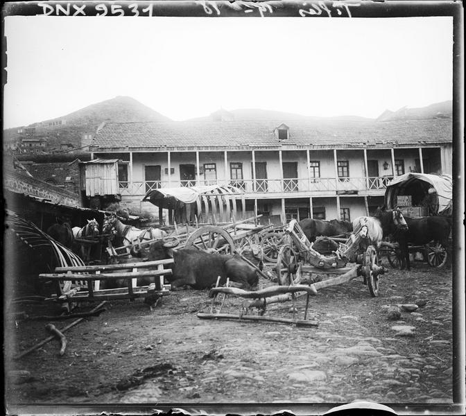 Chevaux et charrettes devant une maison traditionnelle à balcon de bois