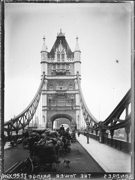 Charrettes hippomobiles chargées de marchandises, traversant le pont