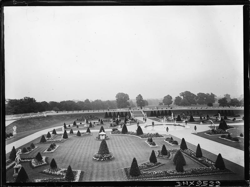 Parterres et arbustes taillés en cônes autour d'un bassin avec jet d'eau