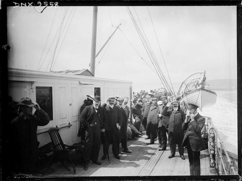 Portrait de groupe : passagers debout sur le pont d'un bateau, devant un canot de sauvetage