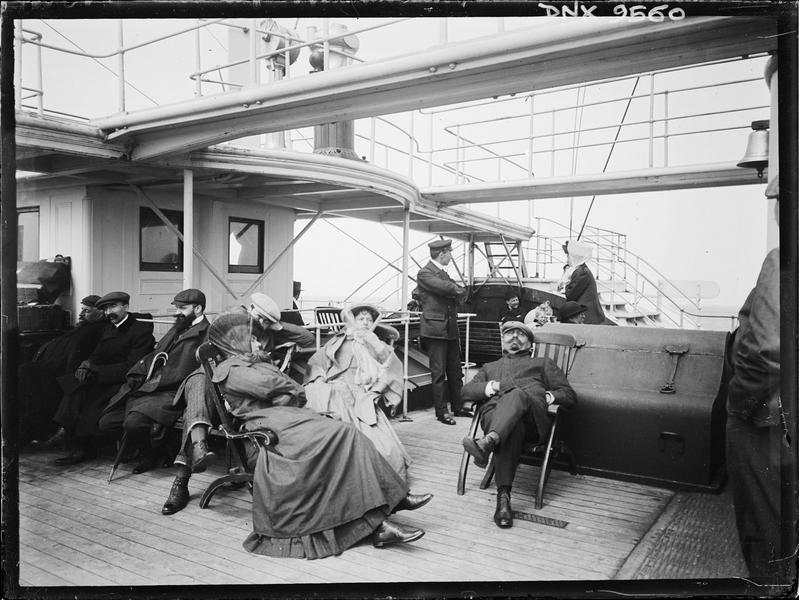 Sur le pont d'un bateau : passagers assis sous les coursives et passerelles