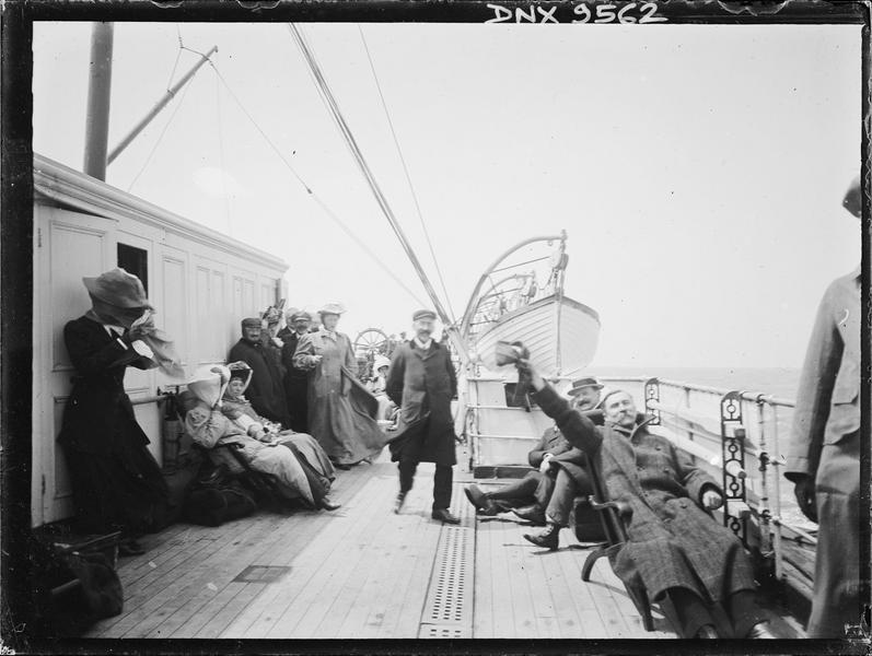 Sur le pont d'un bateau : passagers et canot de sauvetage